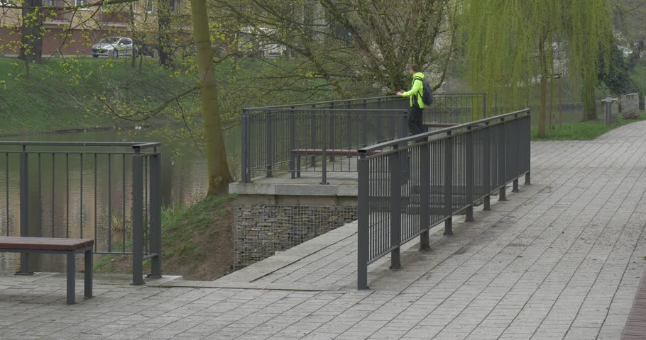 A Tall Man Leans on a Metal Fence, Behind Which a River Begins. the Man is in a Green Zone of a City of Opole (Poland). he Stands on a Bridge and Beholds a Flow of Water. | Shutterstock HD Video #27516403
