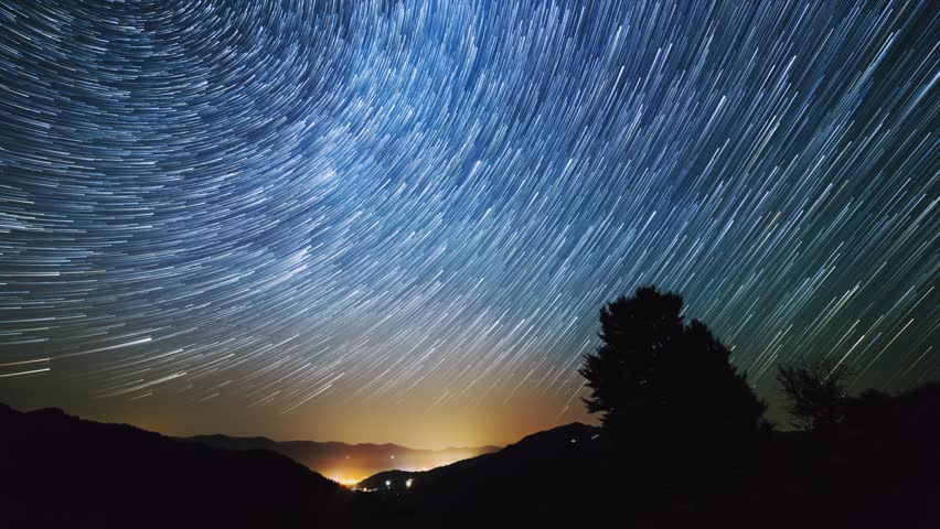 Timelapse of moving star trails in night sky. The Milky Way galaxy rotating over the mountain range in summer time