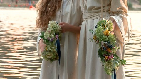 girls stand in the water with wreaths. Slavonic holiday of Ivan Kupala.