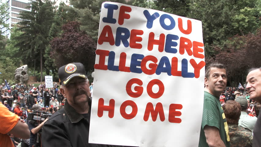 "JUNE 4TH, 2017 - PORTLAND, OREGON: Man holding sign reading ""If you are here illegally, go home,"" supporting Donald Trump's travel ban at Republican rally."