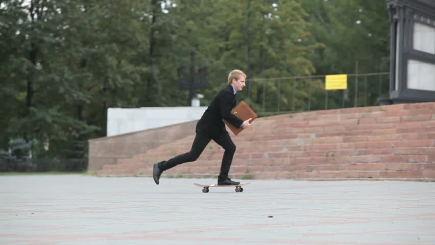 Young businessman skating on board near the building