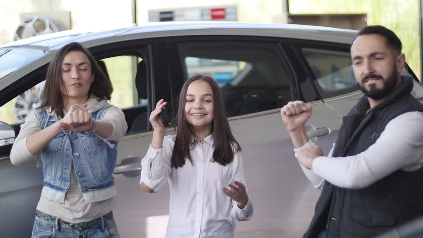 Family celebrating buying a new car. | Shutterstock HD Video #27537316