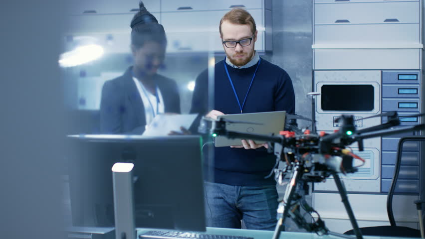 Caucasian Male and Black Female Engineers Working on a Drone Project with Help of Laptop and Taking Notes. He Works in a Bright Modern High-Tech Laboratory. Shot on RED EPIC-W 8K Helium Cinema Camera. | Shutterstock HD Video #27552253