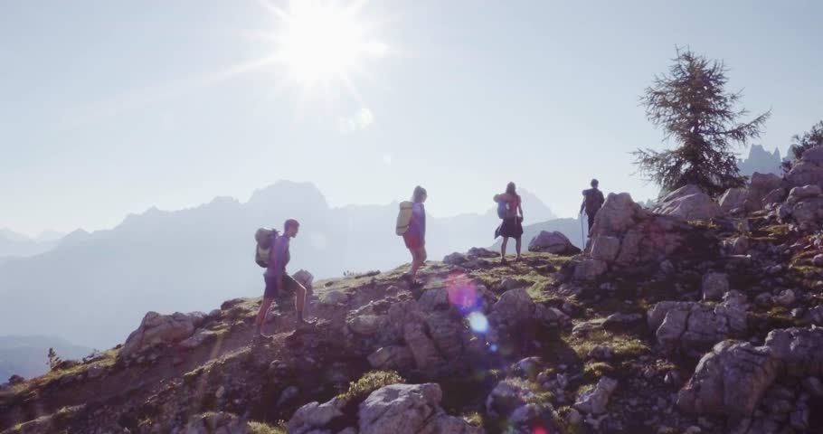 Aerial flight above people hiking along trail path in sunny day. Group of friends summer adventure journey in mountain nature outdoors. Travel exploring Alps, Dolomites, Italy. 4k drone forward video