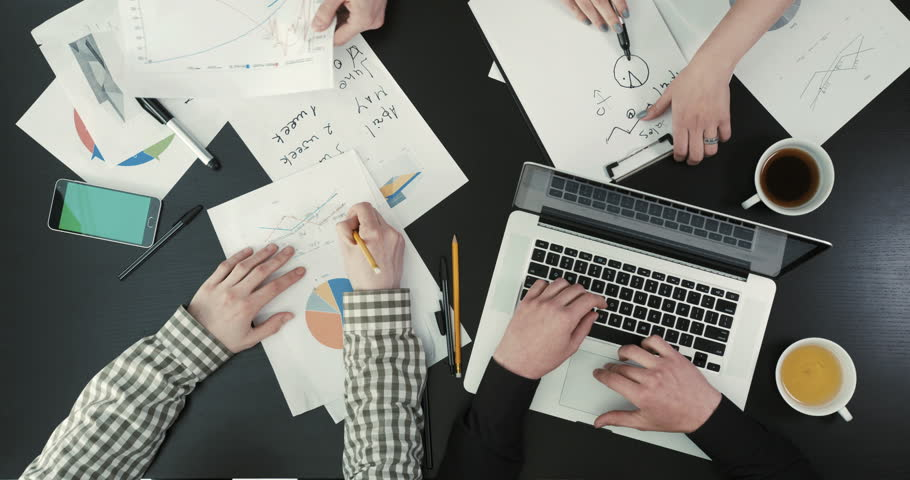 Close-up above view of the businessmen hands sorting the graphics, writing and typing on the laptop. The business composition.   Shutterstock HD Video #27562495