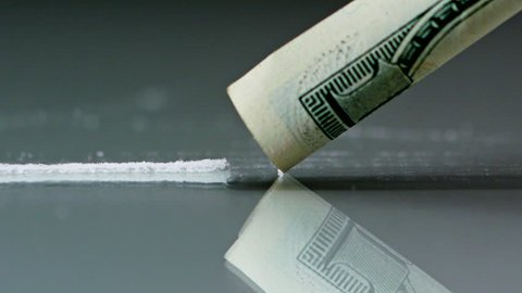 Drug Abuse. A rolled banknote snorting a line of cocaine powder. Problems with drugs concept. Grey background. Close-up macro shot.