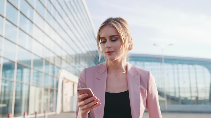 Self-confident hot young blonde girl in an elegant pink jacket walks by the airport terminal and uses her cellphone, smiles happily to the text messages, looks around. Stylish outfit, modern woman.