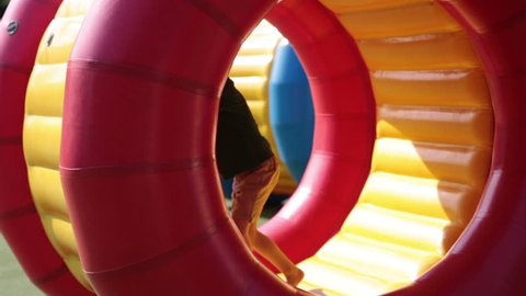 Cute little boys, playing in a rolling plastic cylinder ring with a hole in the middle, outdoor