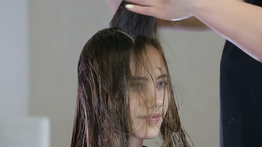 Hairdresser combing and cuting hair of teen girl client in hair salon | Shutterstock HD Video #27577963
