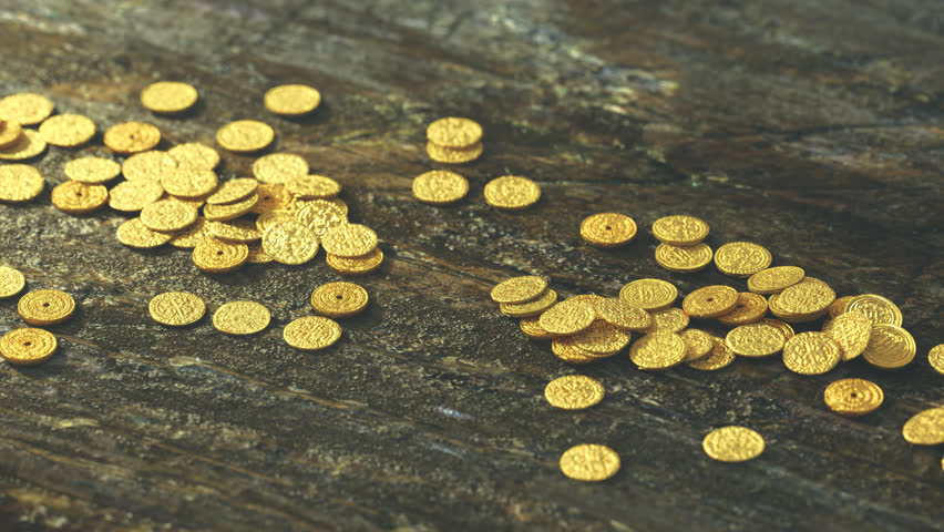 Gold coins falling on the wooden table