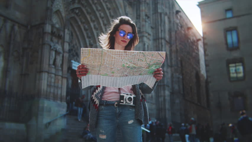 Attractive young woman traveling in Europe and exploring beautiful sightseeing in Barcelona, sunshine lens flare, slow motion, hipster girl wearing glasses and holding tourist map, enjoying holiday  #27590053