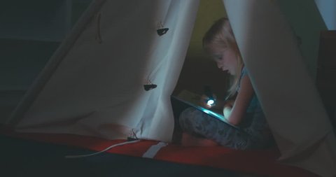 Little blonde Caucasian girl reading a book with a flashlight inside a teepee tent at home. 4K UHD RAW edited footage