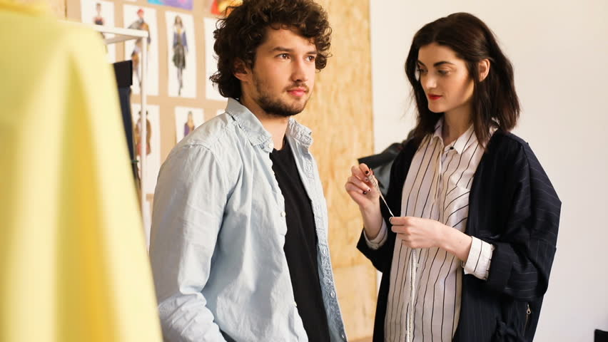 Young stylish designer clothes woman and client man talking about order in the studio | Shutterstock HD Video #27621913