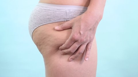 Woman holding cellulite on her butt with no finger sign. Caucasian female hand testing the skin for stretch marks and fat with disapproval gesture. Body control, self confidence and weight loss