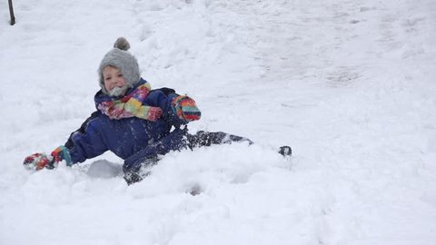 Happy child sleighing, colorful muffler and glove, rolling in the snow, accident, dangerous play