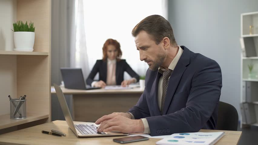 Employee typing on laptop at office desk, answering mobile phone, customer care | Shutterstock HD Video #27706843