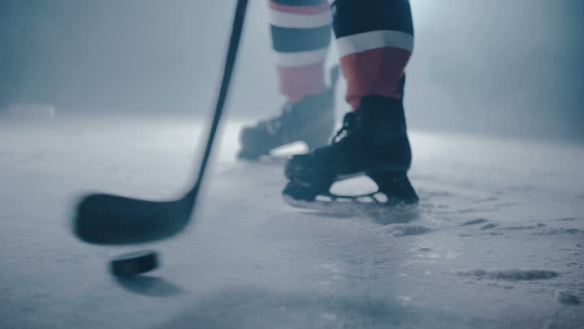 Hockey player hits the puck with a stick on ice close-up | Shutterstock Video #27736873