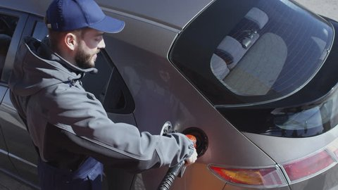 High angle view of gas station attendant taking fuel nozzle at dispenser and filling tank of client's car