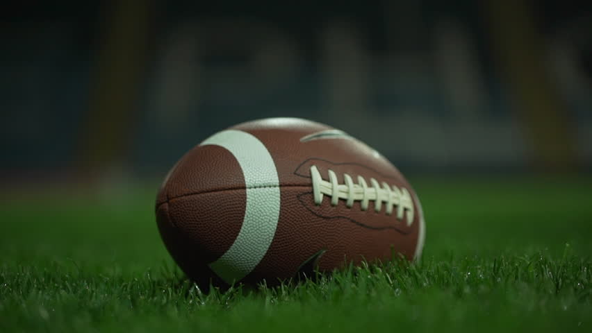 Brown american football ball lying on green grass on stadium. Then player picking it in slowmotion. Close up