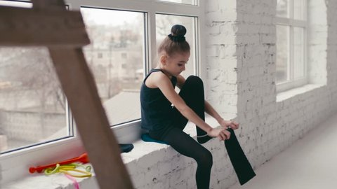 Cute little girl is getting ready to the gymnastics class by the window, puts on her stockings, takes the ball and hurries up to the class. Modern school of classical ballet. Happy childhood.