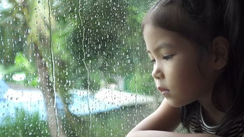 Asian little girl look at rain in a window, slow motion