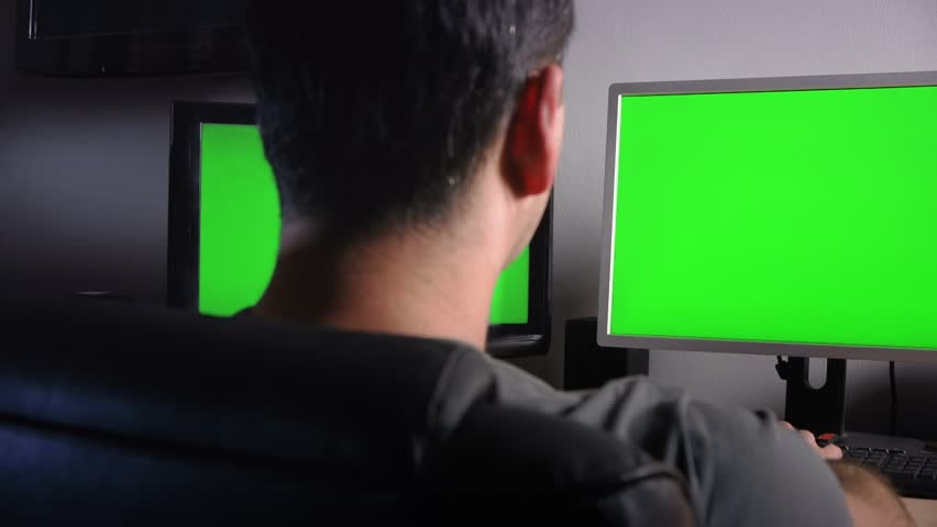 Man working in the office in front of green monitors