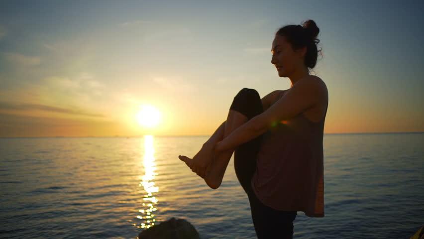 Healthy young flexible girl meditate yoga asanas sea coast sunrise slow motion | Shutterstock HD Video #27764356