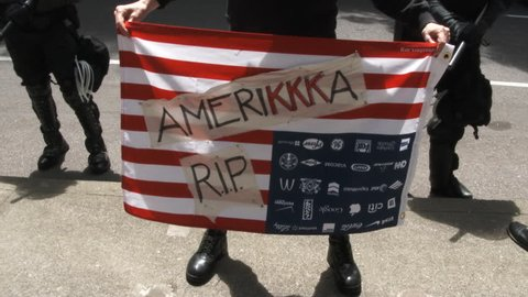 JUNE 4TH, 2017 - PORTLAND, OREGON: Person lifts anti KKK United States of America flag in the air at protest.