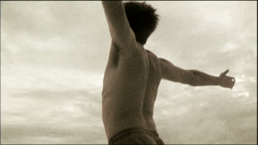 Close up of young man raising hands up into the air, against cloudy sky, black and white