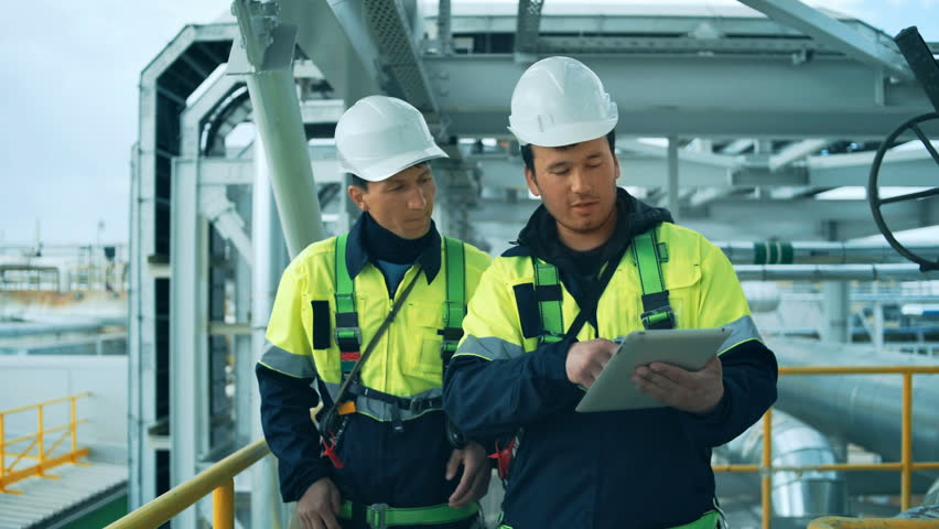 Two factory workers walking and discussion with tablet pc. Industrial background