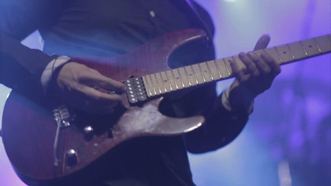 Man lead guitarist playing electrical guitar on concert stage  slow motion