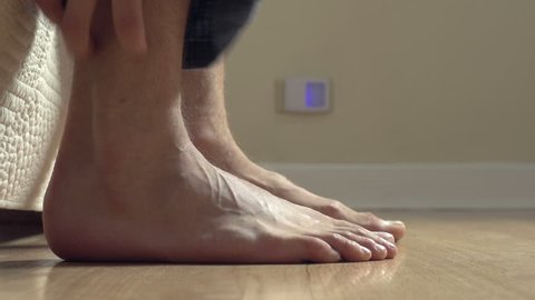 Close up, feet getting out of bed, hitting floor