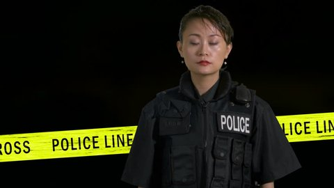 Asian American policewoman pointing pistol  with flashing car siren and boundary tape in background
