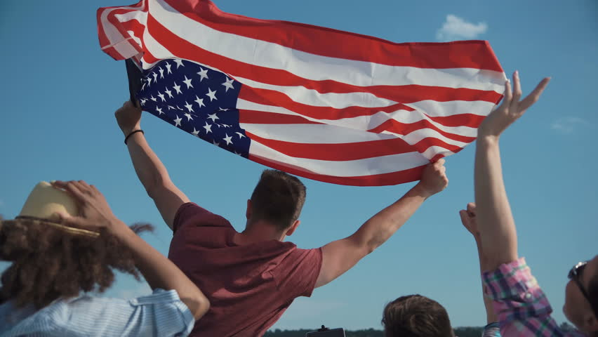 Emotional group of mixed ethnic young friends on board a motor boat along a river laughing and cheering and raise american flag in air. Celebrate an Independence Day on July 4