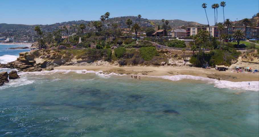 Perfect aerial wide shot of a Malibu California beach with white water waves crashing on the sand from a helicopter point of view showing the sea and coastline in Los Angeles, United States