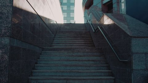 Rear view of young woman going up the stairs in the street. Shot on Red Epic Dragon