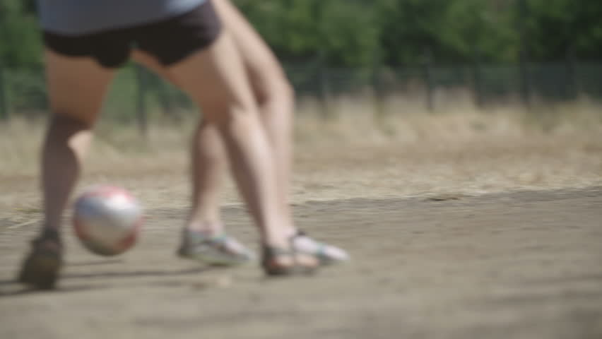 Slow motion tight angle telephoto shot of feet kicking a soccer ball, football, on a dry play field with dust in Patagonia, Chile.