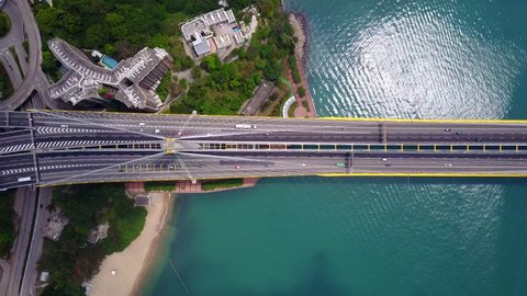 Beautiful top-down shot of traffic on modern cable stayed bridge. Rambler channel bright blue-green water with shining waves under the road. Aerial view of Ting Kau Bridge at Hong Kong.