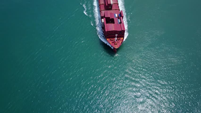 Bow of containership, sailing at beautiful shimmering blue-green water, top-down aerial shot. Camera show front part of post-panamax class vessel, partially loaded with standard intermodal containers