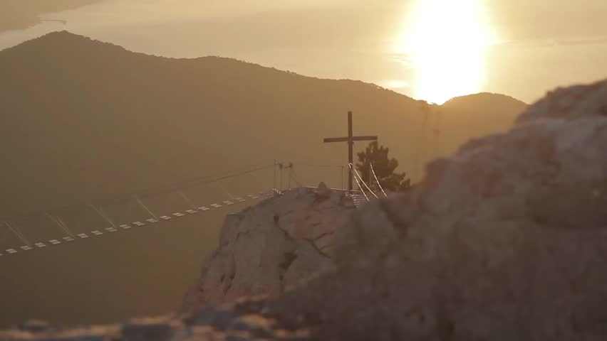 View of the catholic cross and rope ladder over the abyss. Crimea, Ukraine.Ayu Dag Mountain view from the top of Ai Petri mountain during sunrise.
