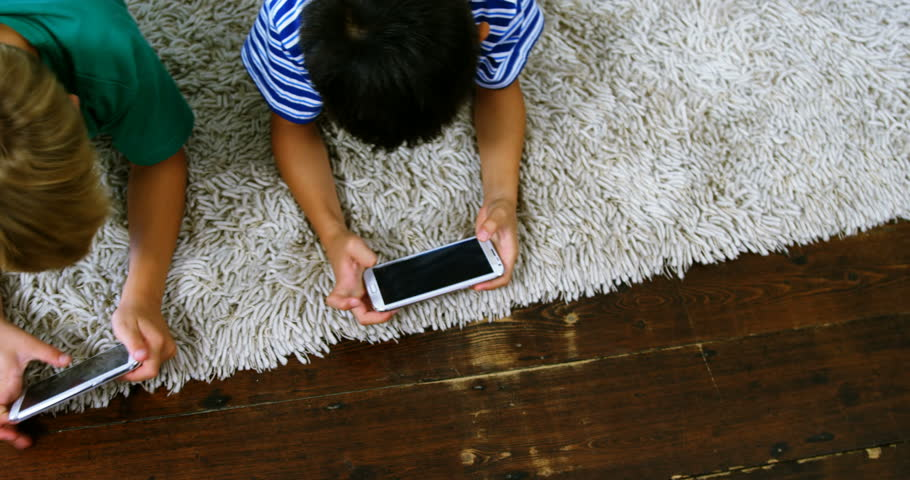 Siblings using mobile phone in living room at home #27934483