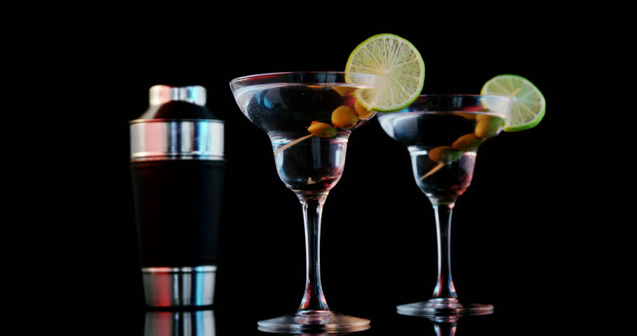 Ice cube falling in two cocktail glasses against black background