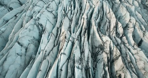 Aerial top view of the ridges of white glacier with black ash. Scenic iceberg in national park in Iceland.
