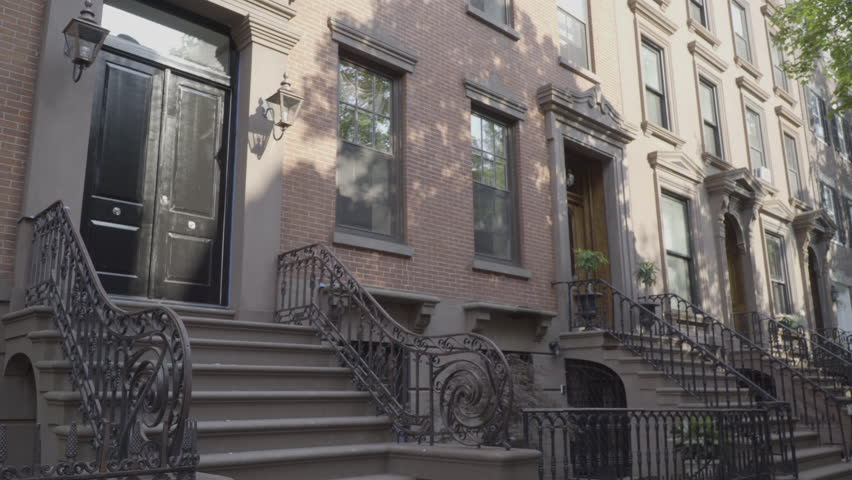 Wide exterior establishing shot outside typical generic Brooklyn style brownstone row of houses. Day time DX video 4K. Famous style architecture expensive luxury real estate living