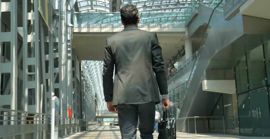 A young handsome businessman (student) in a suit, comes with a briefcase, at the station, at the airport. Concept: a new business, traveling the world, communication, contacts, a new deal, success.  | Shutterstock Video #27992323