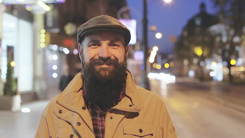 Slow motion portrait of happy young smiling bearded man in the night city street. Bearded caucasian guy looking at camera | Shutterstock HD Video #28001683