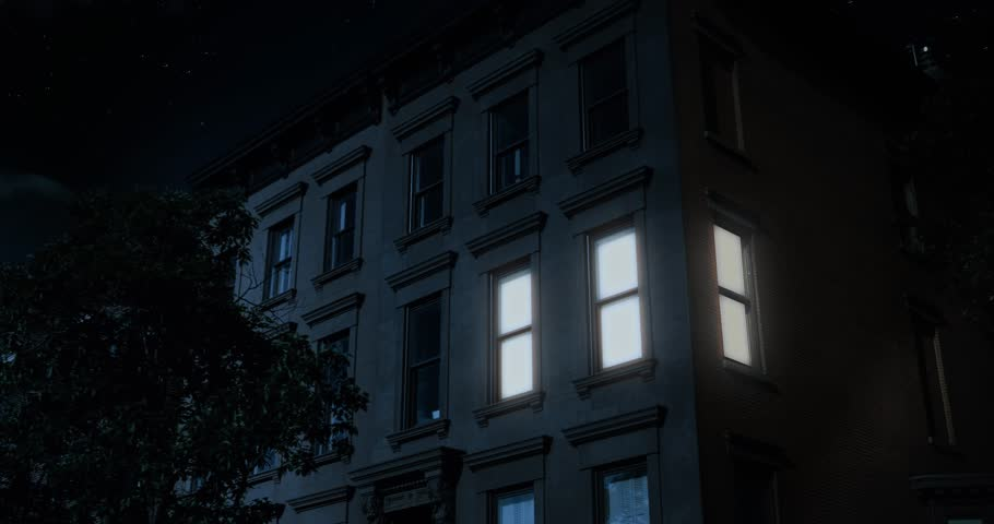 A nighttime exterior establishing shot of the upper floors of a typical Brooklyn brownstone residential home as a room lights up then turns off.   | Shutterstock HD Video #28018423
