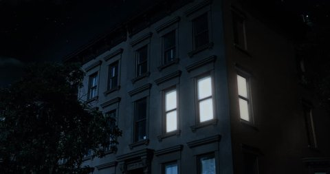 A nighttime exterior establishing shot of the upper floors of a typical Brooklyn brownstone residential home as a room lights up then turns off.