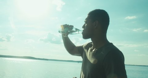Young adult African American man enjoying the view of a large lake on a summer day, drinking water from glass bottle. 4K UHD RAW edited footage