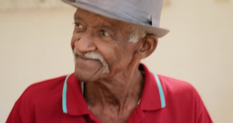 Happy active retired people, old hispanic friends and free time, senior latino men having fun and playing domino at home. Leisure, recreation, retirement. Black man enjoying game